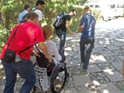 A-team-effort,-pulling-woman-in-wheelchair-up-hill