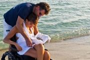 Young-woman-in-wheelchair-on-the-beach-with-her-brother