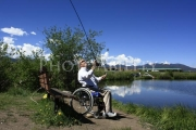 Man-in-wheelchair-casting-his-fishing-rod-into-lake