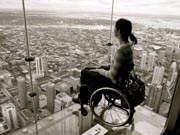 Young-woman-in-wheelchair-on-glass-bottomed-high-rise-observation-tower