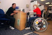 Access-to-services,-Fitness-instructor-and-disabled-woman-at-the-gym-reception,-Special-desk-lowered-for-wheelchair-users,