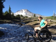 whelchair;woman;female;mountain;snow;spring;snow-drift;forest-trail;disabled;disability;sunny;smiling-woman;accessible;accessibility;accessible-trail