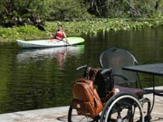 Young-woman-using-wheelchair-kayaking-on-river