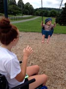 Woman-in-wheelchair-pushing-young-child-in-swing