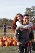 Young-woman-in-wheelchair-gets-piggy-back-ride-in-pumpkin-patch