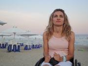 Young-woman-using-wheelchair-on-beach-at-sundown