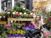 Young-woman-using-wheelchair-at-flower-stall-in-mall