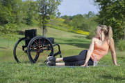 Young-woman-using-wheelchair-exercising-in-park