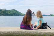 Two-young-women-enjoying-sunny-afternoon-in-riverside-park