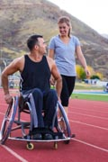 Athletic-man-in-wheelchair-hanging-out-and-exercising-at-an-outdoor-track-and-field-facility-with-group-of-active-friends.
