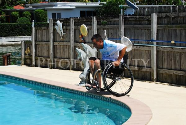 Family fun around the poolMan jumping into his swimming pool in his ...