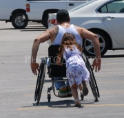 Man-in-wheelchair-being-pushed-by-his-young-daughter
