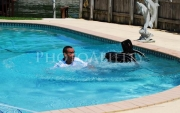 Family-fun-around-the-poolMan-jumping-into-his-swimming-pool-in-his-wheelchair