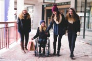 Teenage-girl-using-wheelchair-out-Christmas-shopping-with-her-friends-on-cold-winters-day