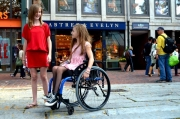 Young-woman-in-wheelchair-in-the-city-with-her-friend