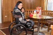 Young-mother-in-wheelchair-having-breakfast-with-her-young-daughter