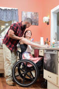 Young-woman-using-wheelchair-cooking-in-her-adapted-kitchen