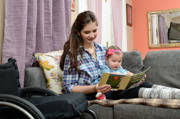 Young-woman-using-wheelchair-reading-to-her-baby