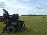 Power-wheelchair-at-grass-airfield-with-glider-in-the-background