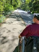 Man-using-wheelchair-on-suburban-footpath
